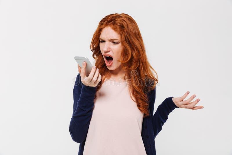 Senhora nova irritada do ruivo que fala pelo telefone celular e que grita fotos de stock royalty free