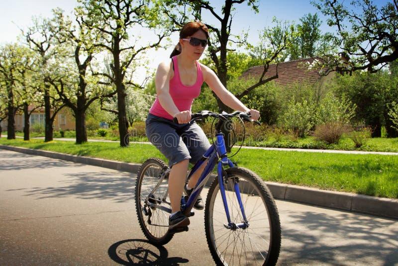 Senhora nova que conduz uma bicicleta fotos de stock