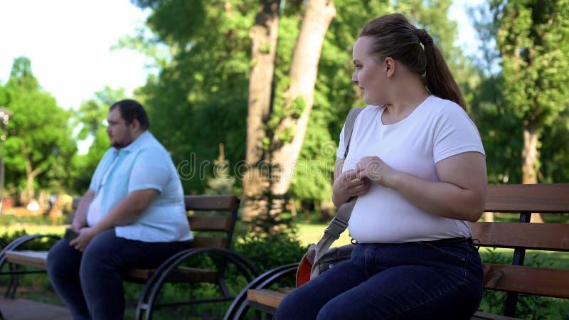 Senhora obeso que flerta com o homem incerto gordo, receoso obter familiar, complexo imagens de stock royalty free