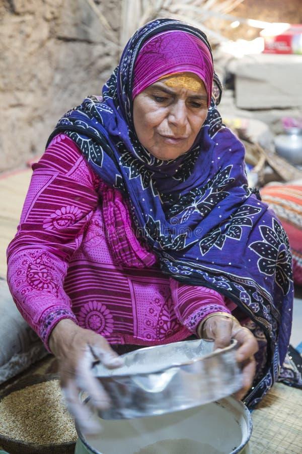 Senhora omanense no equipamento do iraditional com uma peneira para preparar a farinha fotografia de stock