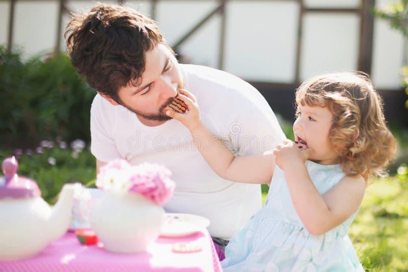 Senhora pequena bonito que joga o tea party com seu pai de inquietação foto de stock royalty free