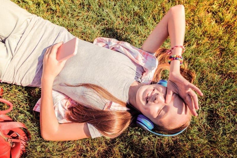 Senhora pequena feliz que encontra-se em uma grama na roupa leve imagem de stock royalty free