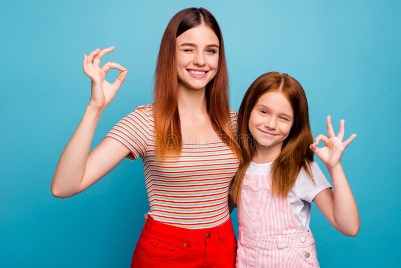 A senhora pequena foxy bonita e sua mamã o símbolo do okey que da exibição veste a roupa ocasional isolaram o fundo azul fotografia de stock