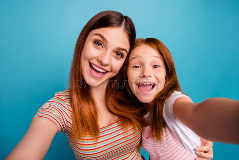 Senhora pequena foxy engraçada e sua mamã que fazem consideravelmente selfies vestir o fundo azul isolado da roupa ocasional fotos de stock