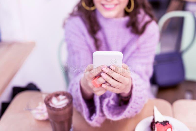 Senhora positiva de sorriso que leva seu telefone celular branco imagens de stock royalty free