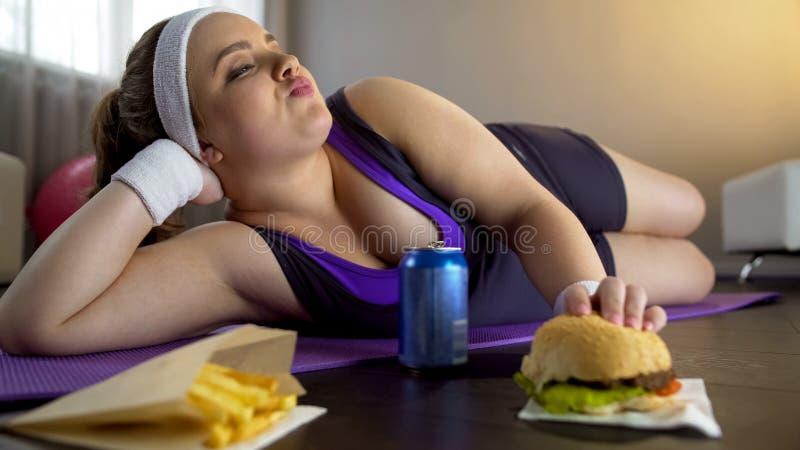 Senhora presumido gorda que come a comida lixo em vez do exercício, falta da motivação foto de stock