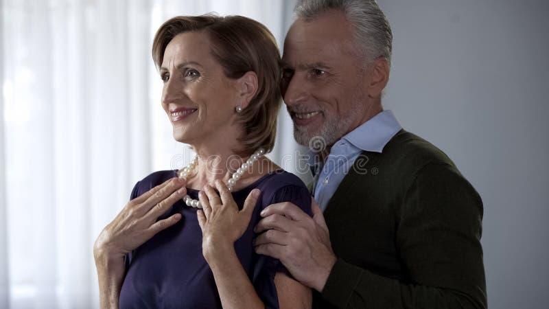 Senhora que admira o presente precioso do marido de amor, sorriso superior feliz dos pares fotografia de stock royalty free
