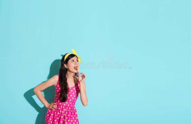 Senhora que come o pirulito dos doces que olha a área vazia foto de stock