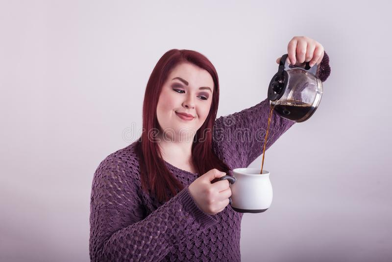 Senhora que derrama o café preto da garrafa à caneca fotos de stock royalty free