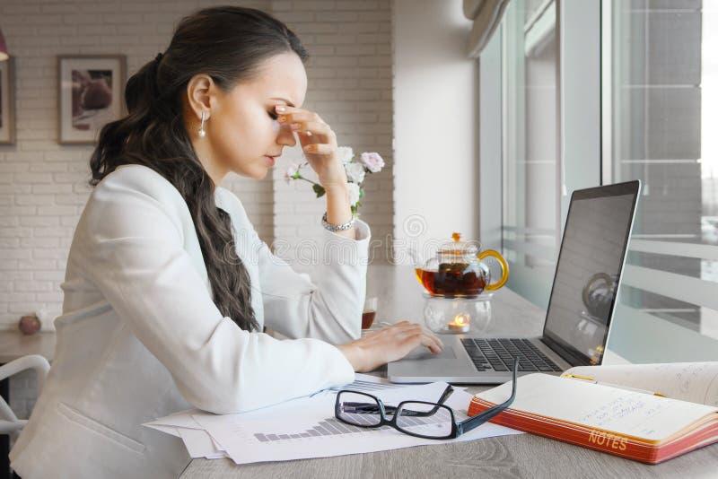 Senhora que guarda o nariz com os olhos fechados devido ao esforço foto de stock royalty free