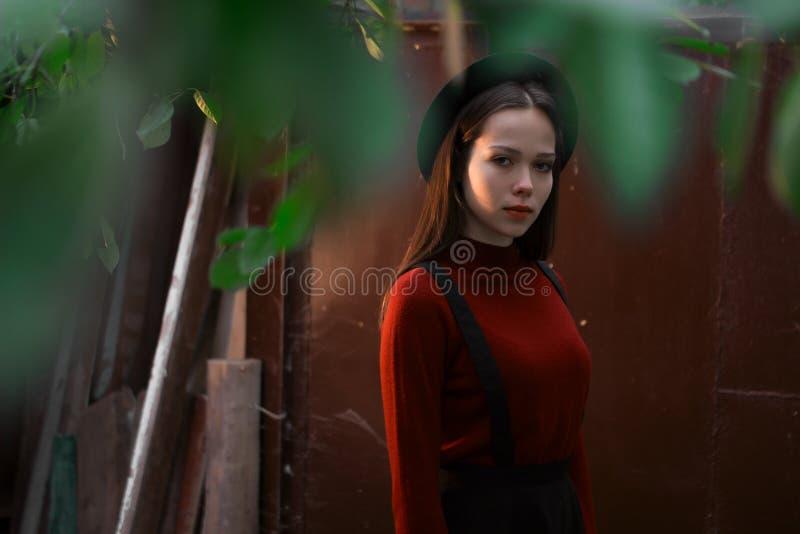 Senhora que levanta em uma obscuridade - fundo vermelho Chapéu largo-brimmed à moda vestindo modelo A menina olha a câmera Fôrma  foto de stock