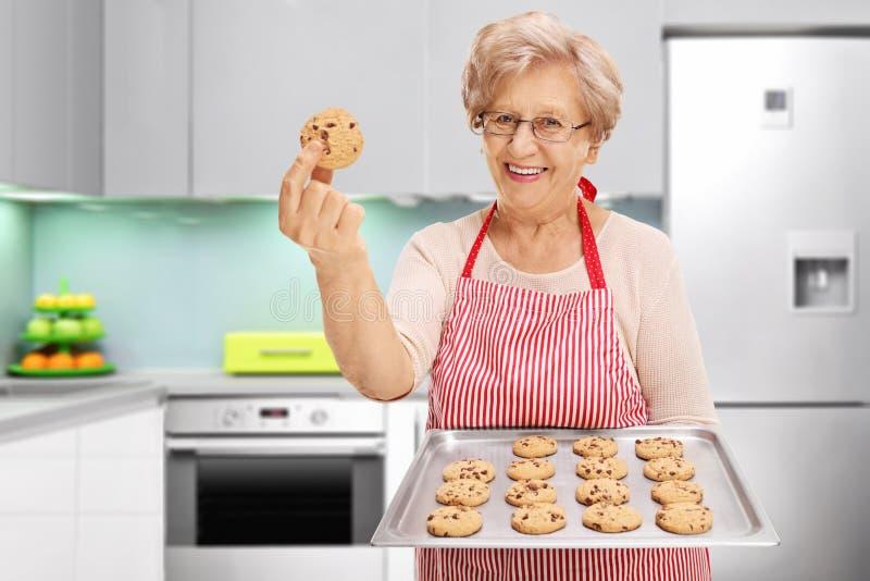 Senhora que mostra lhe cookies dos pedaços de chocolate fotografia de stock