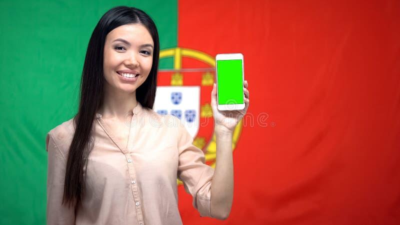 Senhora que mostra o telefone com tela verde, bandeira portuguesa no fundo, app do curso fotos de stock royalty free