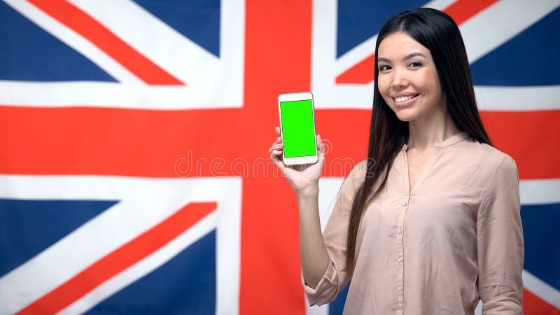 Senhora que mostra o telefone com a tela verde contra a bandeira britânica no fundo, app fotografia de stock