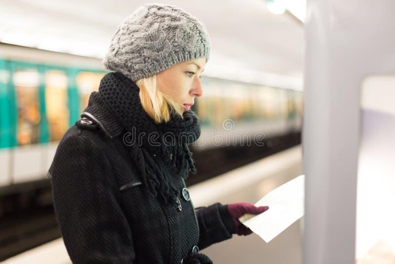 Senhora que olha no painel do mapa do transporte público fotografia de stock