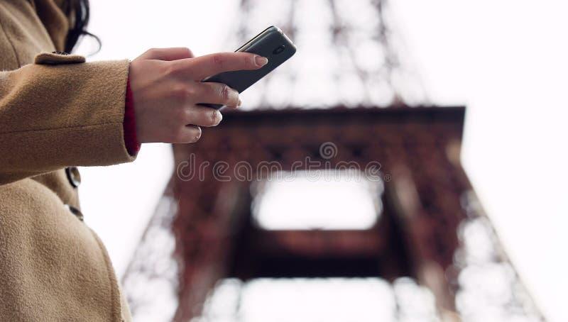 Senhora que procura o número do táxi no smartphone app e que chama para registrar o veículo fotografia de stock