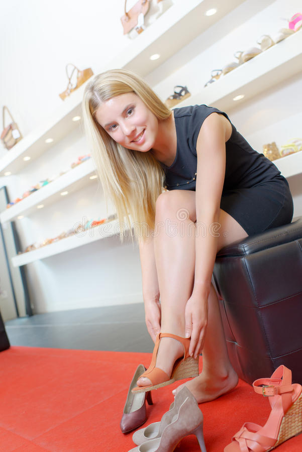 Senhora que tenta em sapatas na loja imagem de stock royalty free