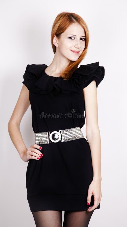 Senhora red-haired nova no levantamento preto do vestido imagem de stock