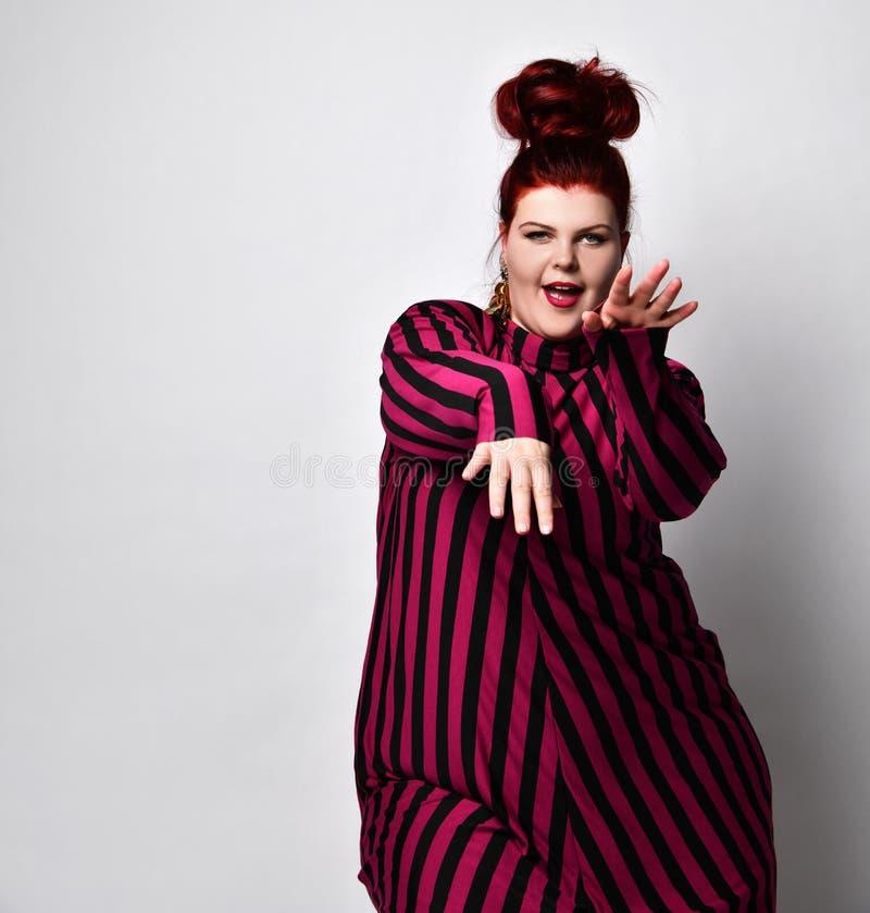 Senhora ruiva obesa em vestidos e brincos listrados Ela lhe estende a mão enquanto posava de lado isolada em fundo branco fotos de stock