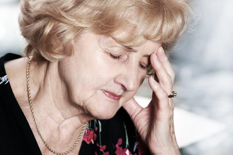 Senhora sênior com dor de cabeça fotografia de stock