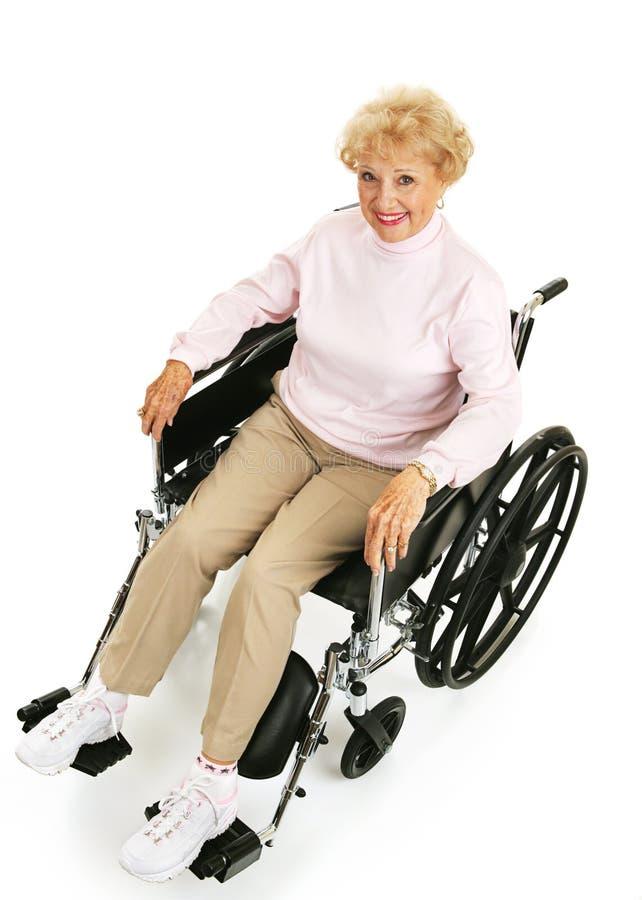 Senhora sênior de sorriso na cadeira de rodas fotografia de stock
