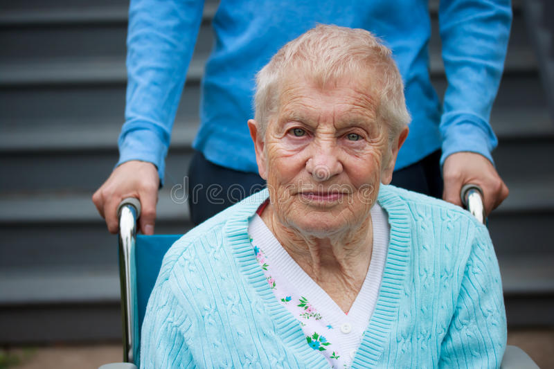 Senhora sênior na cadeira de rodas com guarda foto de stock royalty free