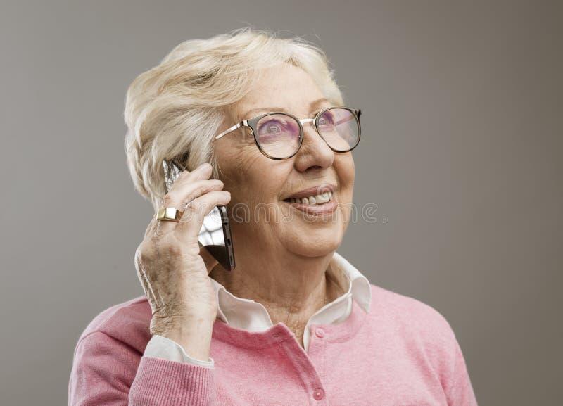Senhora s?nior feliz que fala no telefone fotografia de stock royalty free