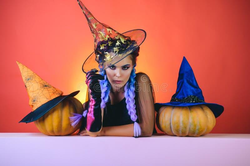 Senhora 'sexy' do vampiro da forma do encanto com traje da bruxa Mulher nas bruxas chapéu e traje que aponta a mão - mostrando pr imagens de stock royalty free