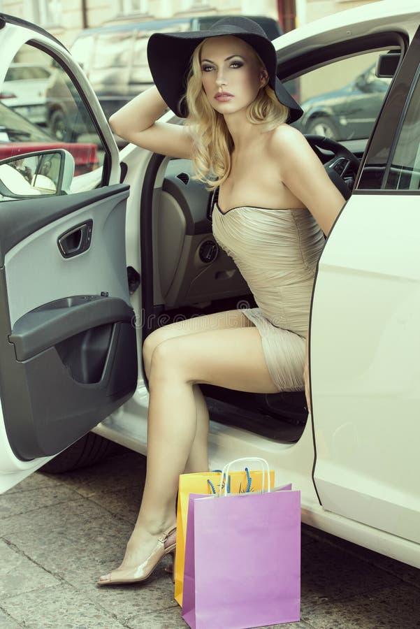 A senhora 'sexy' loura sai do carro fotos de stock