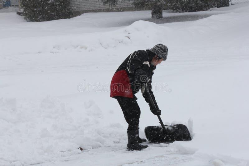 Senhora Shoveling Snow fotos de stock royalty free