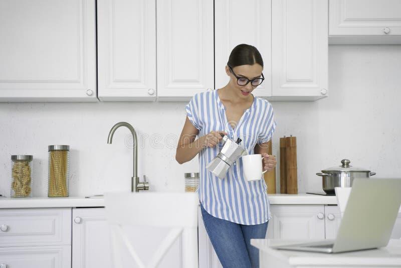 Senhora sorridente tomando café quente na foto da estoque da cozinha imagens de stock