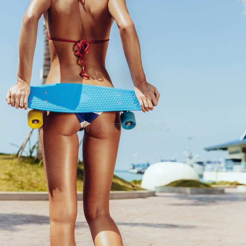 Senhora suntanned 'sexy' que fica com placa azul da moeda de um centavo no streat foto de stock