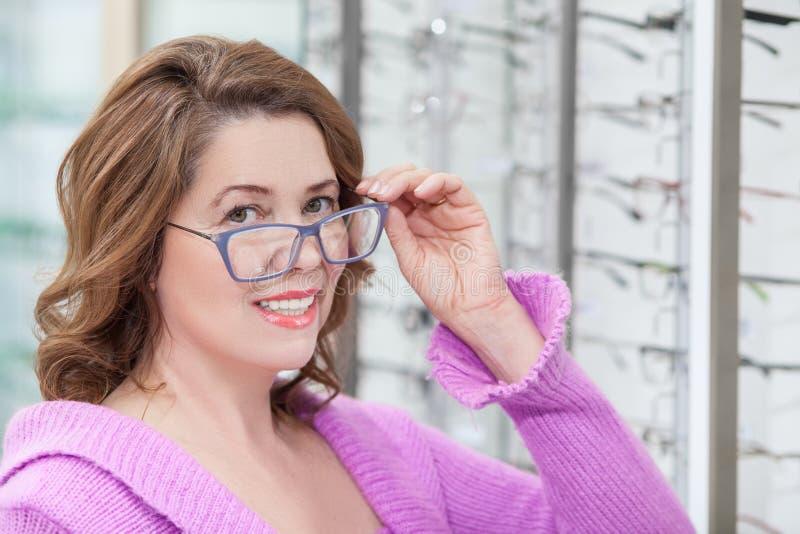 A senhora superior alegre está comprando o eyewear novo fotos de stock royalty free