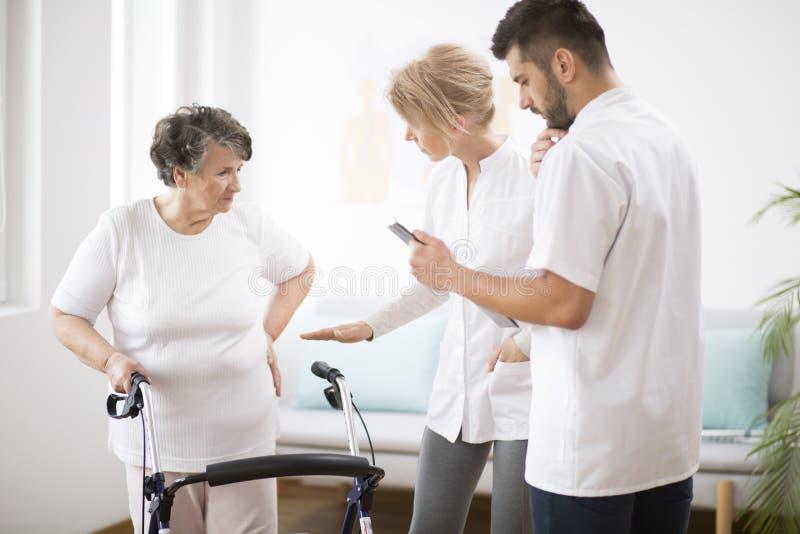 Senhora superior cinzenta com o caminhante durante a fisioterapia com o doutor f?mea profissional e a enfermeira masculina foto de stock royalty free