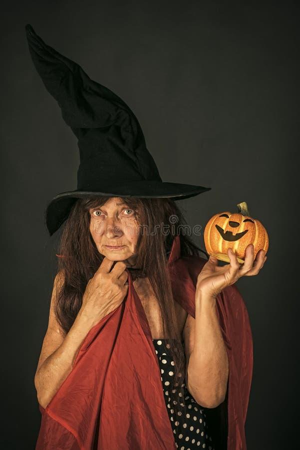 Senhora superior de Dia das Bruxas que guarda a abóbora no fundo preto imagens de stock royalty free