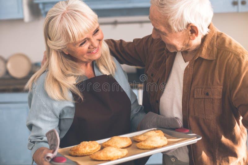 Senhora superior de inquietação que leva a pastelaria doce a seu esposo fotografia de stock