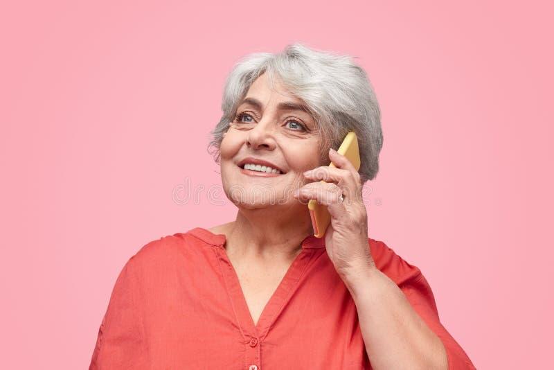 Senhora superior de sorriso que fala no smartphone imagens de stock royalty free