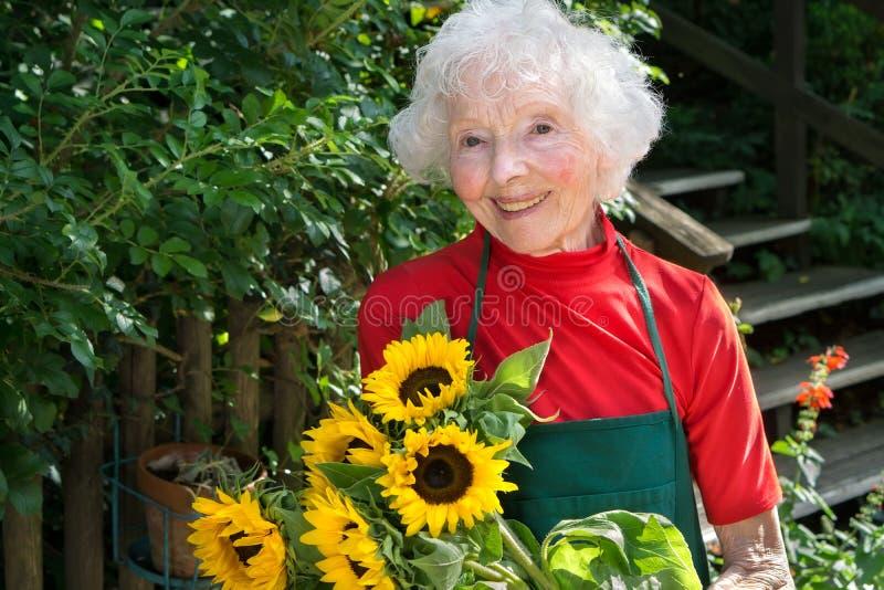 Senhora superior de sorriso que jardina em sua jarda fotografia de stock royalty free
