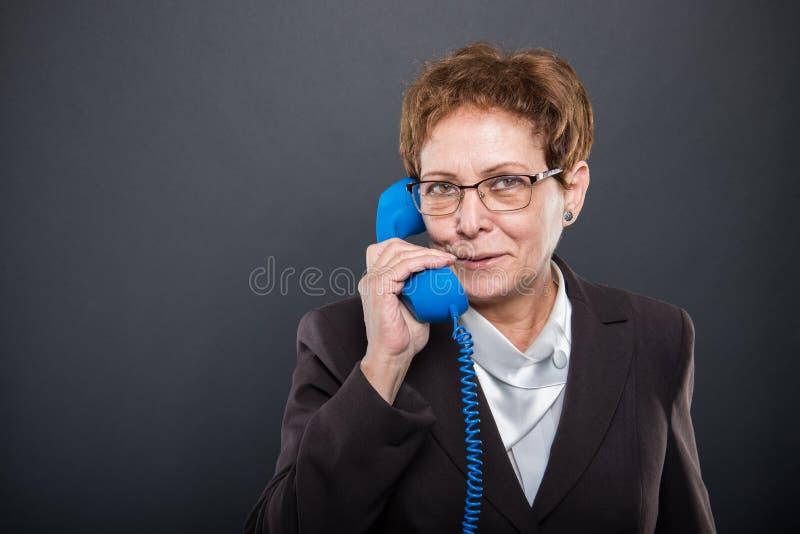 Senhora superior do negócio que fala no receptor de telefone azul grande foto de stock