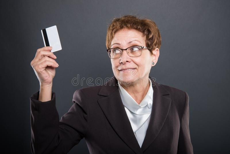 Senhora superior do negócio que guarda e que olha o cartão de crédito imagens de stock
