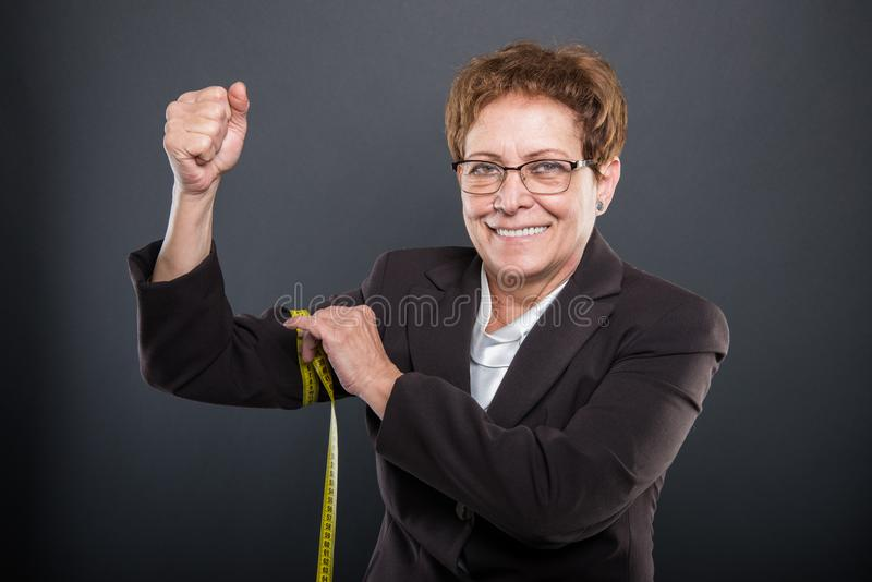 Senhora superior do negócio que mede seu bíceps com fita imagens de stock royalty free