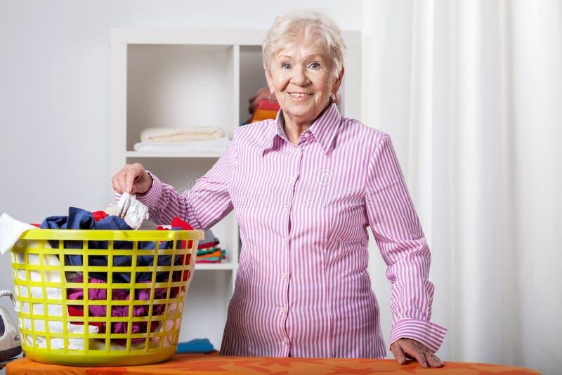 Senhora superior durante a lavanderia de dobramento imagem de stock
