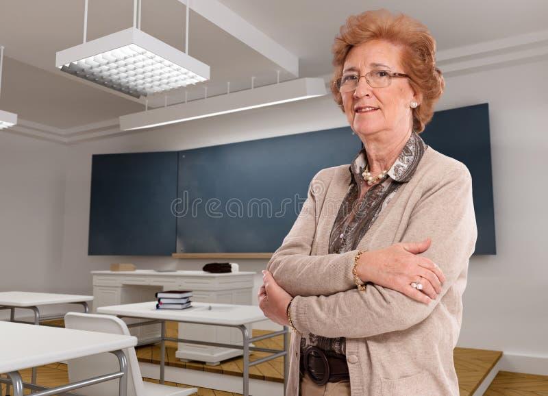 Senhora superior em uma sala de aula fotografia de stock royalty free