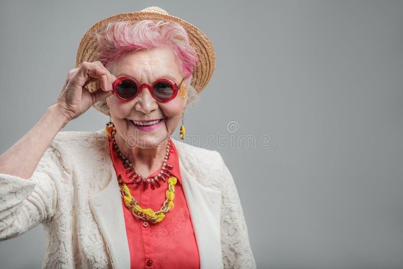 Senhora superior engraçada que olha a câmera imagens de stock