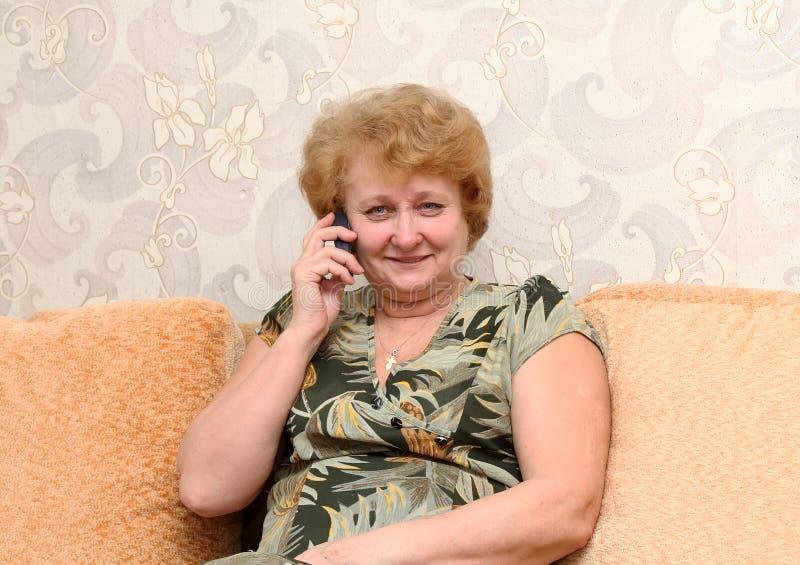 A senhora superior fala por um telemóvel. fotografia de stock