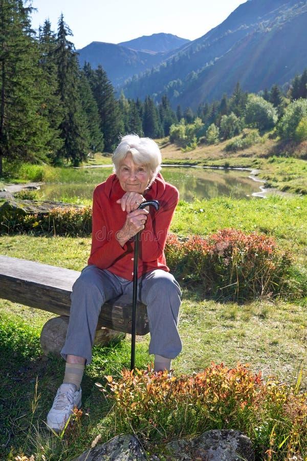 Senhora superior feliz que aprecia as montanhas imagens de stock