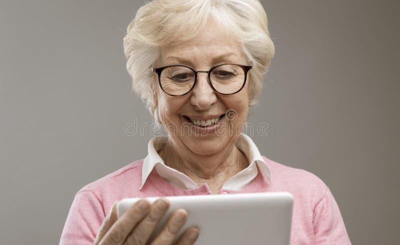 Senhora superior feliz que usa uma tabuleta digital fotos de stock