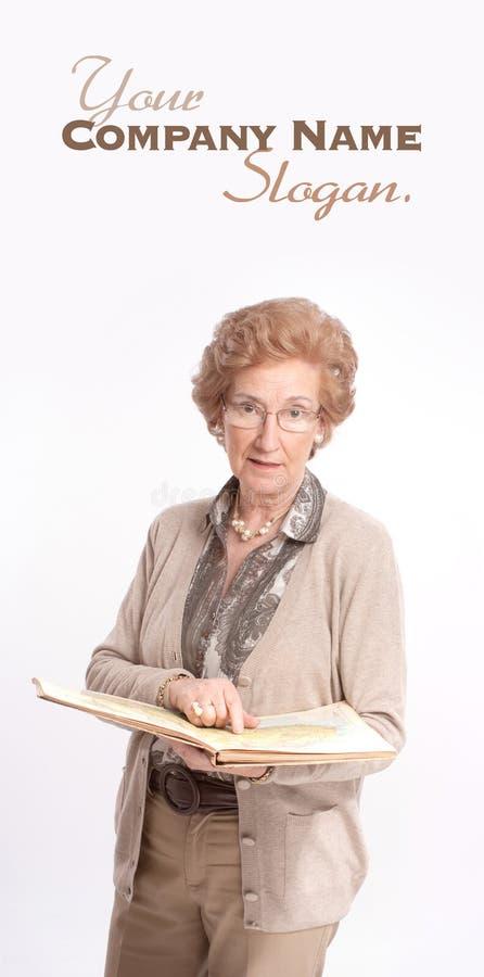 Senhora superior que aponta uma página em um livro imagens de stock royalty free