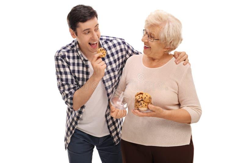 Senhora superior que dá cookies a um homem imagem de stock royalty free