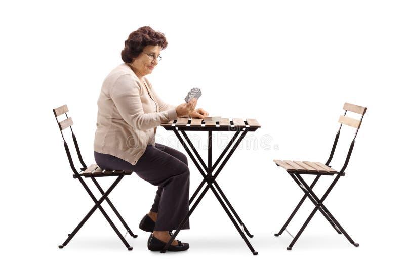 Senhora superior que senta-se em uma tabela e em cartões de jogo foto de stock
